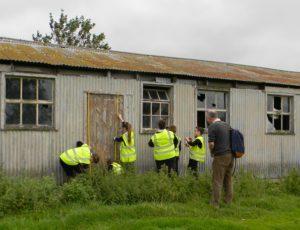 Schoolchildren surveying a hut